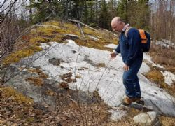 Image of Peter Spitnaly reviewing the pegmatite exposure