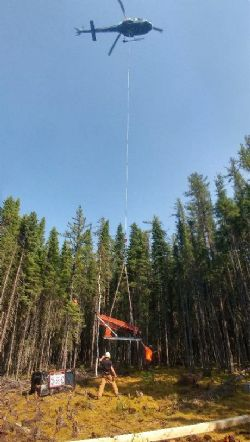 Image showing the helicopter airlifting drilling equipment onto the first drill pad at the Kasagiminnis Lake Property